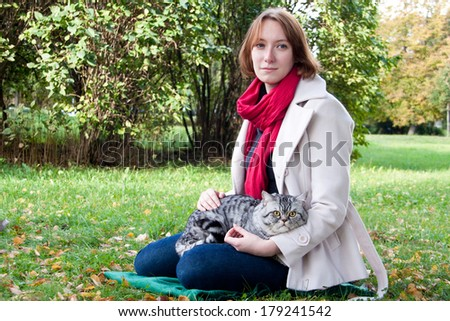 Young woman holding Scottish straight shorthair cat - stock photo