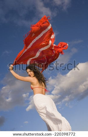Young woman holding shawl over her head in the wind - stock photo