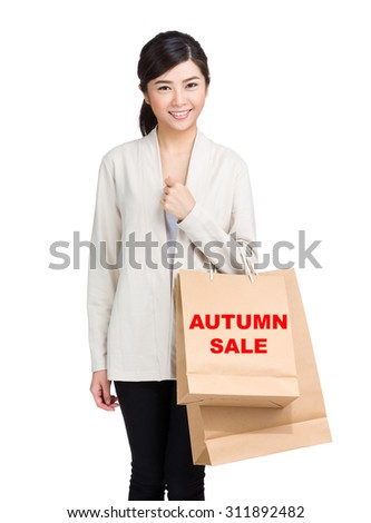 Young woman holding shopping bag and showing autumn sale