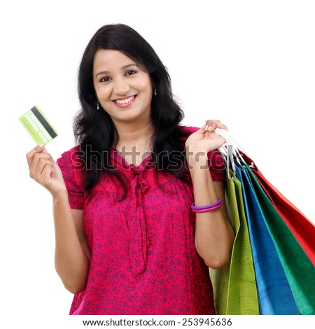 Young woman holding shopping bags and credit card - stock photo