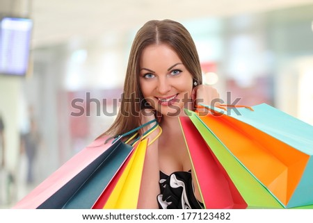 young woman holding shopping bags and smiling at camera - stock photo