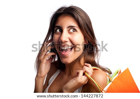 young woman holding shopping bags and speaking on the phone - stock photo