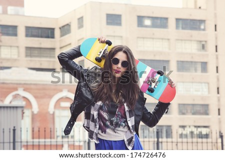 Young woman holding skateboard in the city.  - stock photo