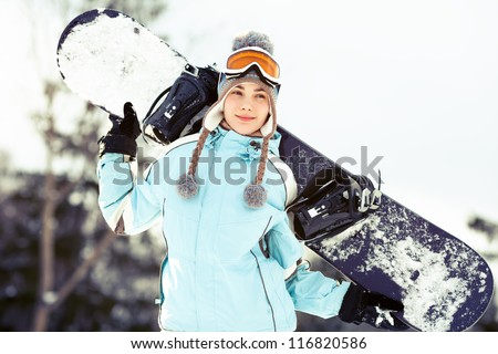Young woman holding snowboard on her shoulders, she's looking away and smiling, copy space, close up