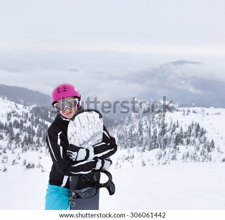 Young woman holding snowboard, she's looking away and smiling, copy space, close-up