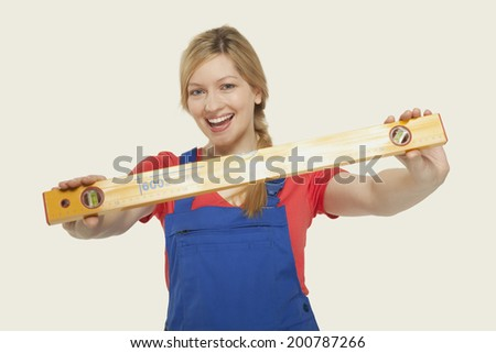 Young woman holding spirit level smiling - stock photo