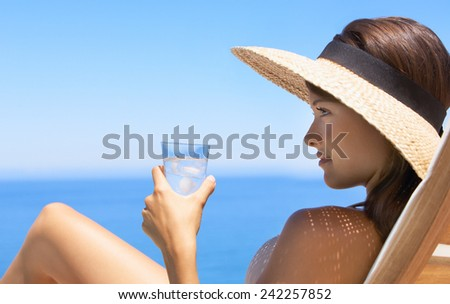 Young woman holding the glass with water while sitting on a deck chair - stock photo