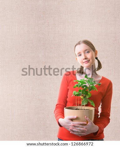Young woman holding the plant in the pot over textured background - stock photo