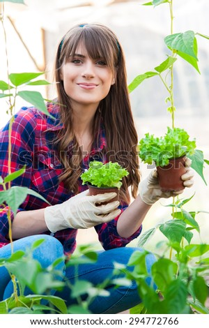 Young woman holding two salad seedlings in greenhouse. - stock photo