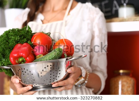 Young woman holding vegetables standing in kitchen - stock photo