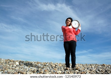 young woman holding wall clock over blue sky in the beach