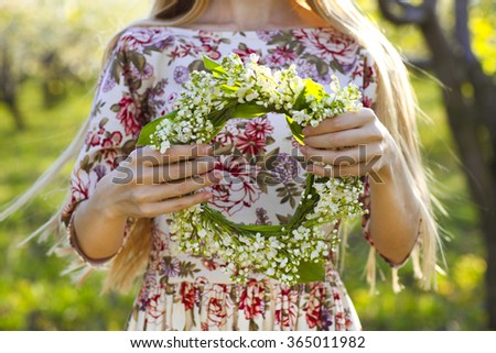 Young woman holding wreath from lily of the valley in her hands. Close up
