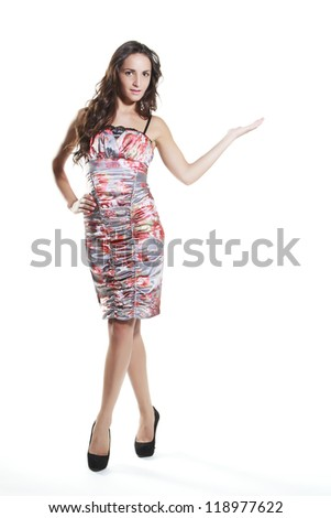 young woman holding your amazing product in hand and smiling against white background - stock photo