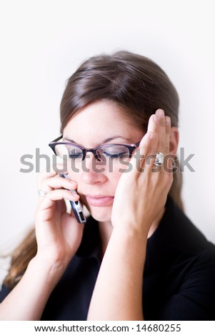 Young woman holds her opposite ear as she talks on a cell phone. It looks as if she is stressed or in concentration. She is very modern and well dressed.