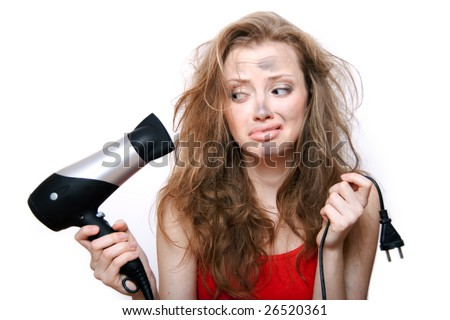 Young woman holds  plug and hairdryer. Electrical explosion. - stock photo