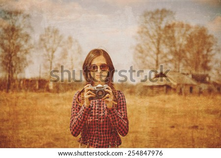 Young woman holds vintage photo camera outdoor. Vintage image - stock photo
