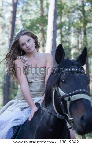 Young woman horseback riding in forest - stock photo