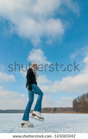 Young woman ice skating on a frozen lake, Funny view because of the wide-angle  perspective  - stock photo