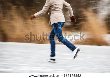 Young woman ice skating outdoors on a pond on a freezing winter day (motion blurred image)