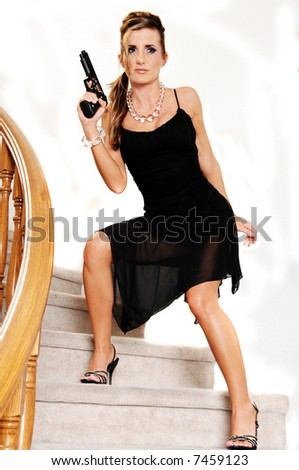 Young woman in a black cocktail dress and crystal necklace and bracelet sneaking down the stairs with a 45 caliber handgun - stock photo