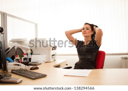 Young woman in a black dress is sitting at a desk in the office