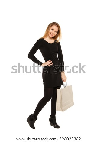 Young woman in a black dress with shopping bags, isolated on a white background. - stock photo