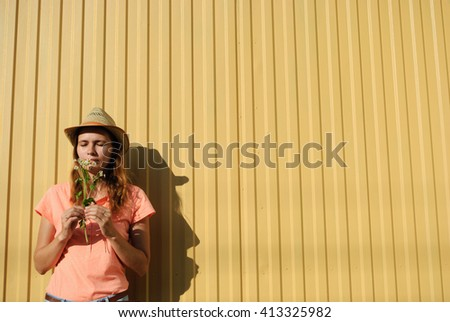 young woman in a cowboy hat smelling a bouquet of chamomile - stock photo
