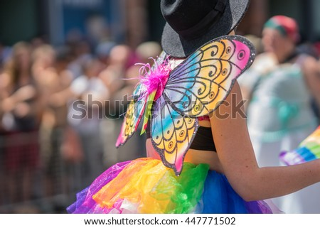 Young woman in a crowd celebrating Pride Parade. Wearing colorful rainbow butterfly wings and a bright tutu skirt. Supporting marriage equality and LGBT rights.  - stock photo