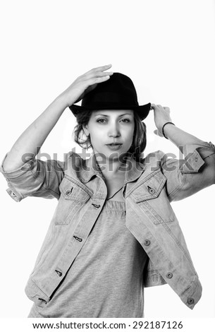 Young woman in a denim jacket and a black hat. Black and white portrait - stock photo