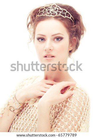 Young woman in a diadem and bracelets of gold on white background.