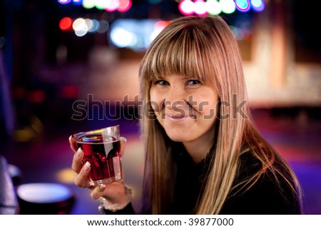 young woman in a discotheque is having a drink - stock photo