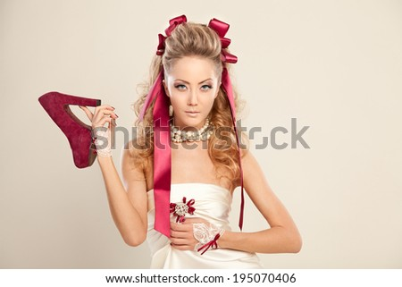 Young woman in a doll style with red bows, holding a red shoe. Studio photography. - stock photo