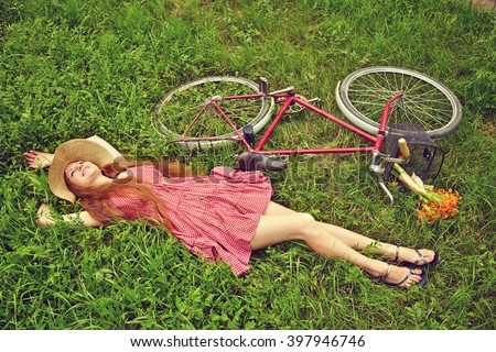 young woman in a dress and hat with a bike lying on the grass in a summer park - stock photo