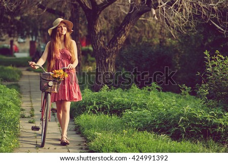 young woman in a dress and hat with a bike with flowers in a basket in a summer park - stock photo