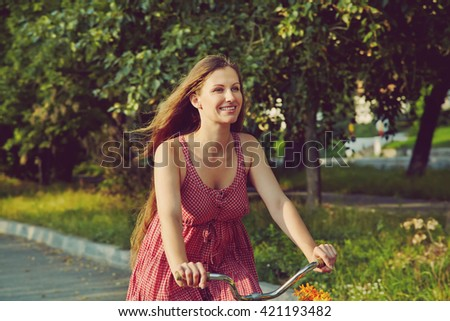 young woman in a dress rides a bike in a summer park - stock photo
