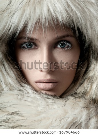 Young woman in a furry hood. Beauty Fashion Model Girl in a Fur Hat - stock photo