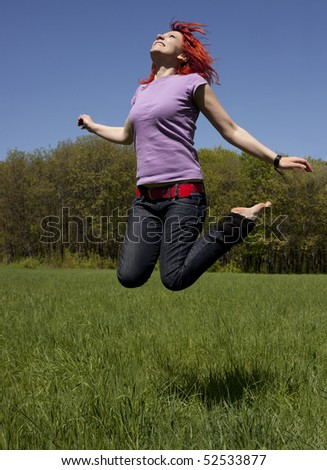 Young woman in a green landscape jumping