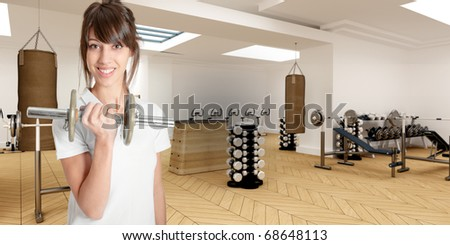 Young woman in a gym lifting a dumbbell - stock photo
