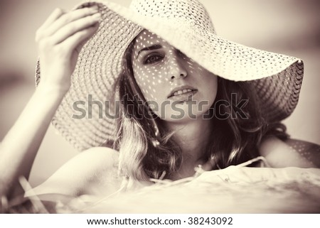 Young woman in a hat portrait. Soft yellow tint.