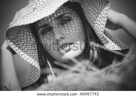 Young woman in a hat rural portrait. Black and white. - stock photo
