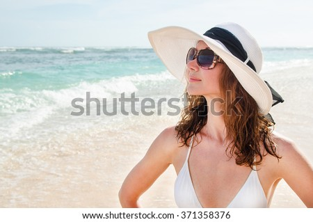 Young woman in a hat walking on the azure beach Bali. Stock image.