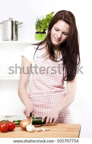 young woman in a kitchen cutting cucumber for salad - stock photo