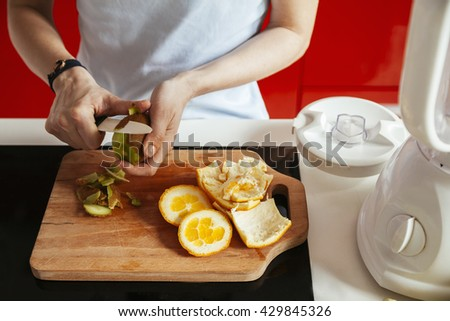 Young Woman In A Kitchen Cutting Fruit For A Smoothie