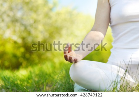 Young woman in a lotus position in a flourishing park - stock photo