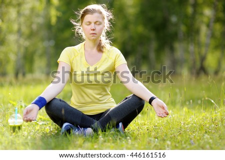 Young woman in a lotus position in a park. Resting after workout. Green detox smoothie.  - stock photo