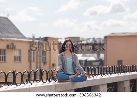Young woman in a lotus position on the city parapet - stock photo