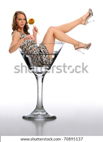 Young Woman in a Martini Glass holding an olive against a neutral background - stock photo