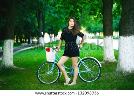 young woman in a park posing with a retro bicycle - stock photo