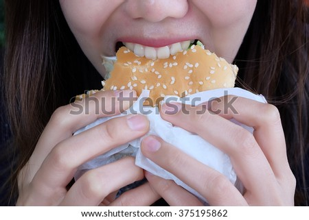 young woman in a restaurant eating a fast food hamburger / focus on the burger - stock photo