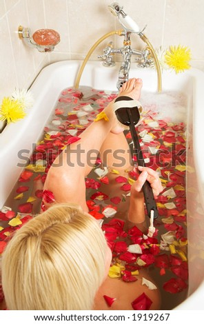 Young woman in a rose-petal bath exfoliating her feet with a brush